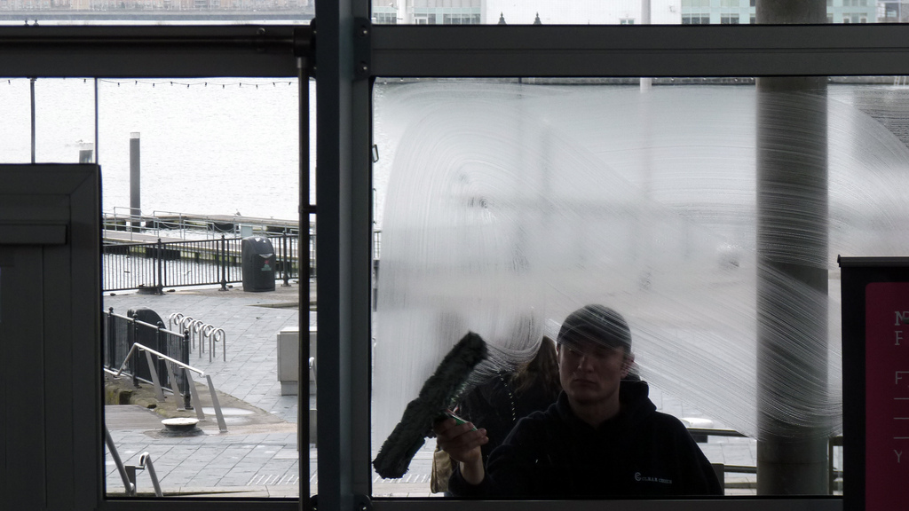 Photo of a man cleaning a window